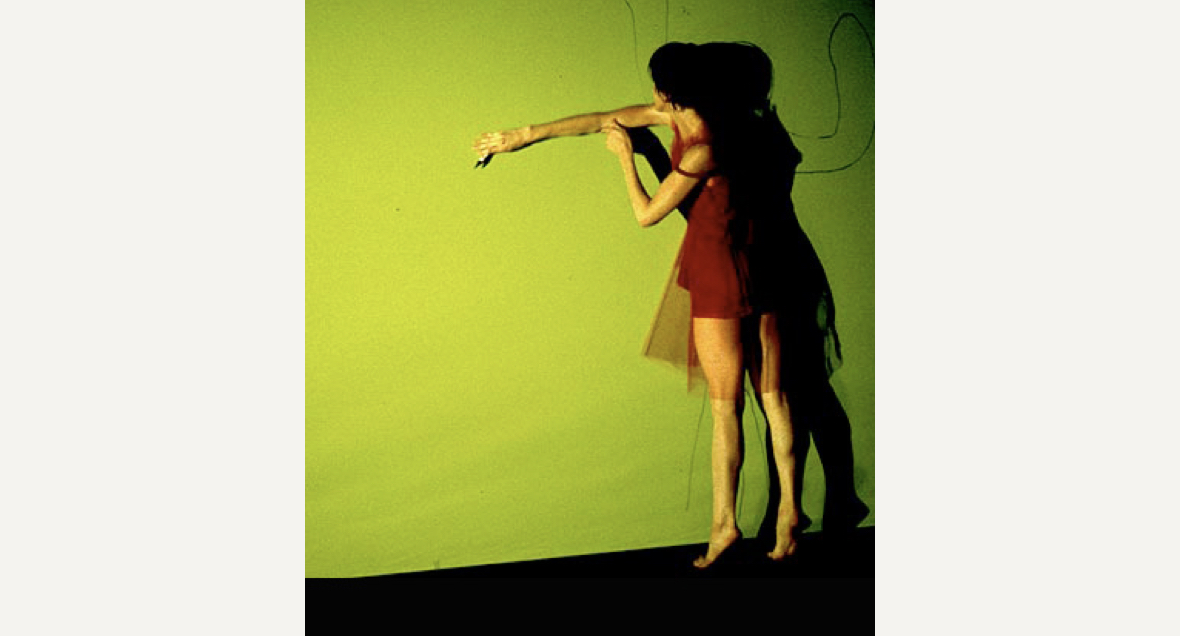 A dancer in a short red outfit stands facing a bright green wall on demi pointe and their right arm reaching across their body along the wall