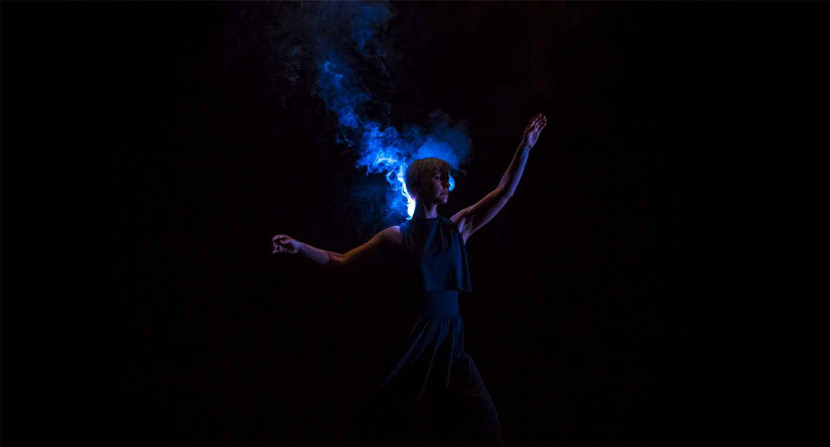A dancer stands, lit from behind, with arms outstretched while smoke  curls around her head.