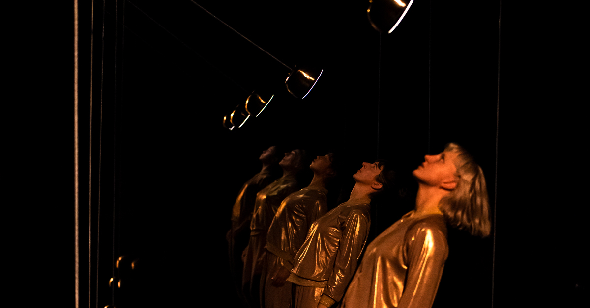 Dancers in gold tracksuits stand in a row with their heads tilted back as pendulum swing above their faces.