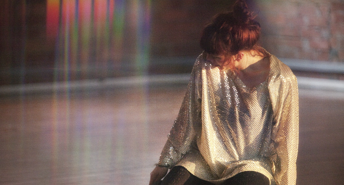 A woman kneels and looks away from the camera to her right in a sparkly dress. The light in the image creates a rainbow effect on the left