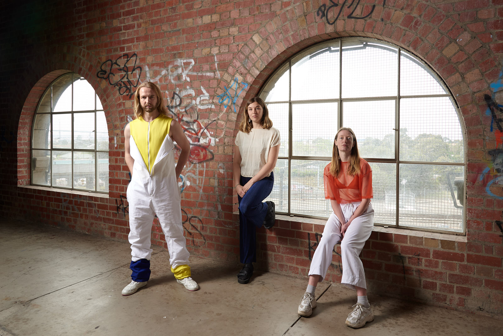 Choreographers Geoffrey Watson, Siobhan McKenna and Sarah Aiken stand in front of a semi-circular window and brick wall
