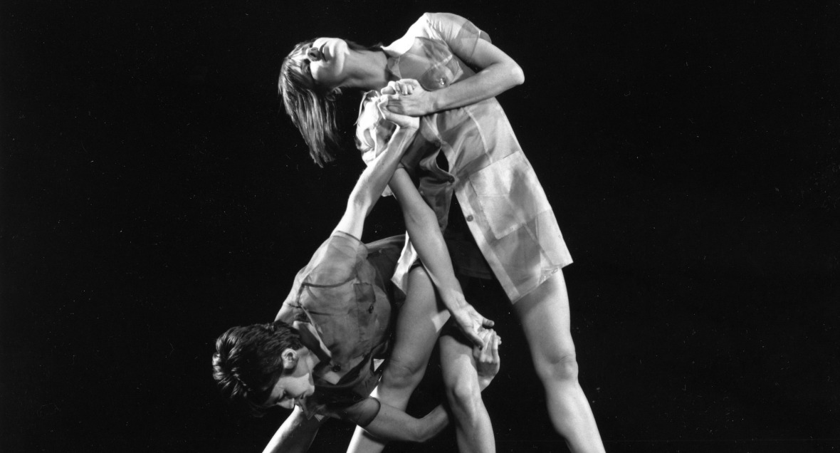 A greyscale image of two dancers striking angular postures at different levels that entangle with each other
