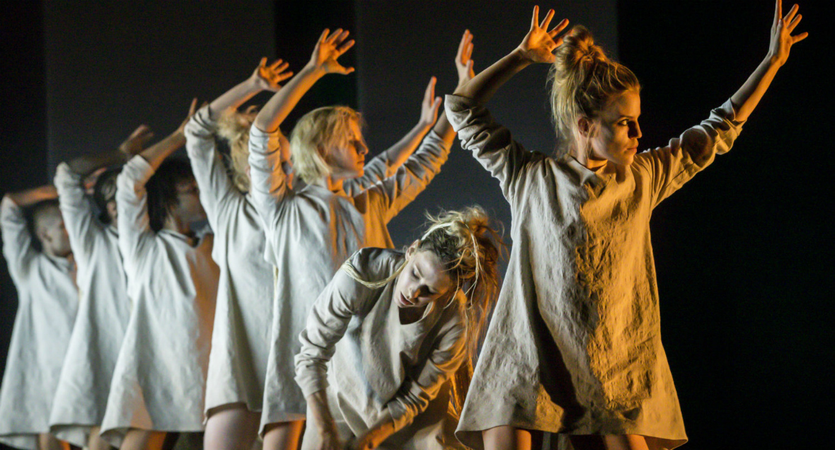 Dancers stand in a line with their arms held high above their head.