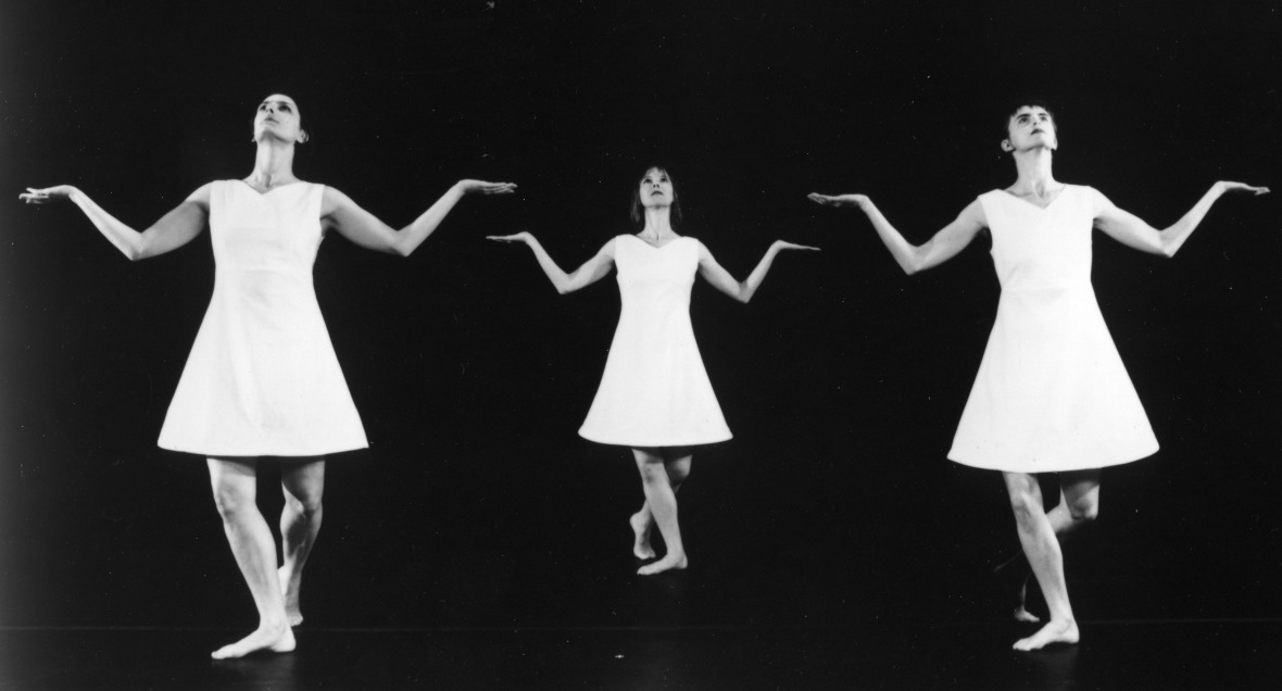 Three dancers in short triangular white dresses stand in identical postures, with arms bend from their sides, palms up and looking up
