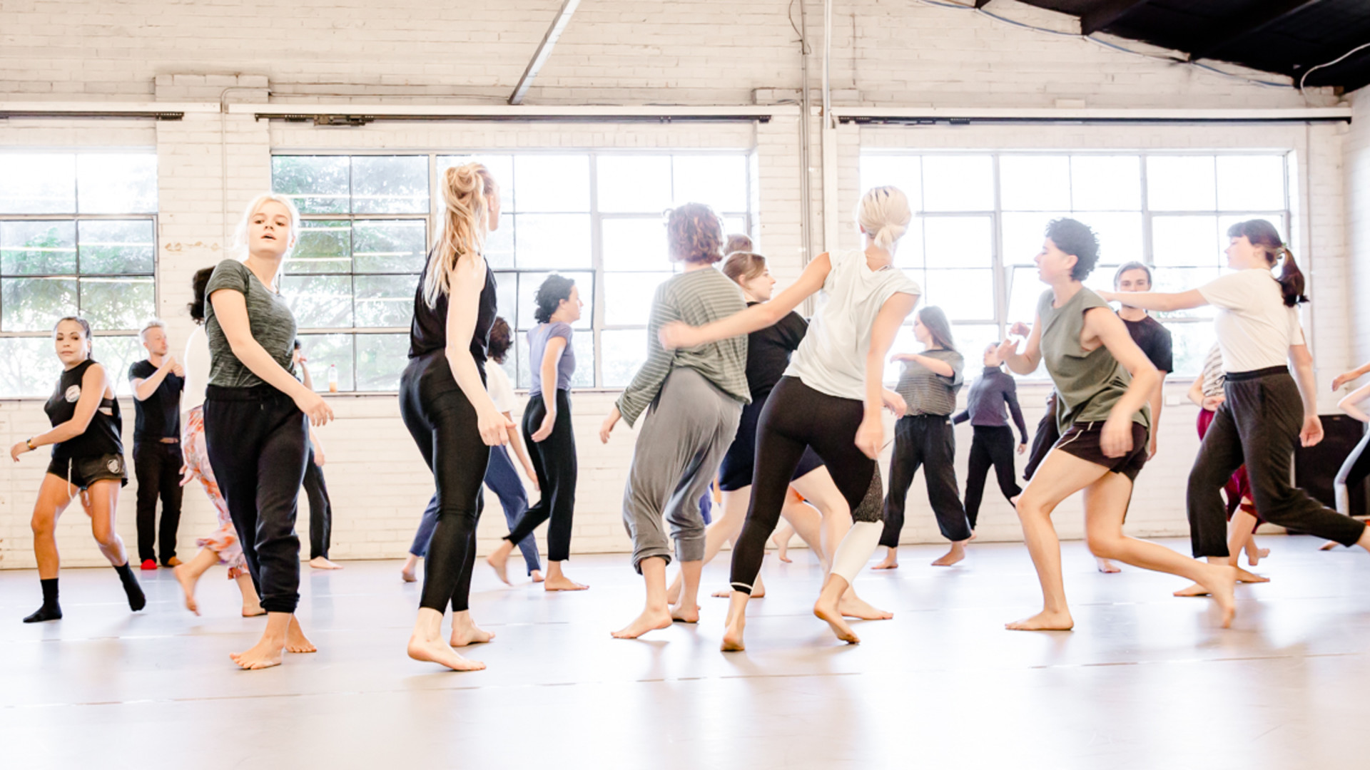 Dancers run, lean and walk in a light-filled grey-floored dance studio. Contemporary Dance Class, Melbourne. Lucy Guerin Inc Jo Lloyd