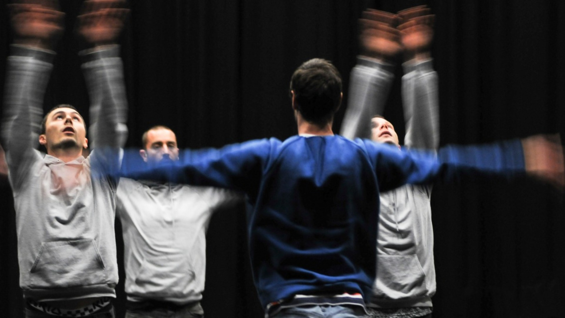 4 dancers, 3 in grey tops facing 1 in a blue top, wave their arms energetically while looking up or forward in front of a black wall