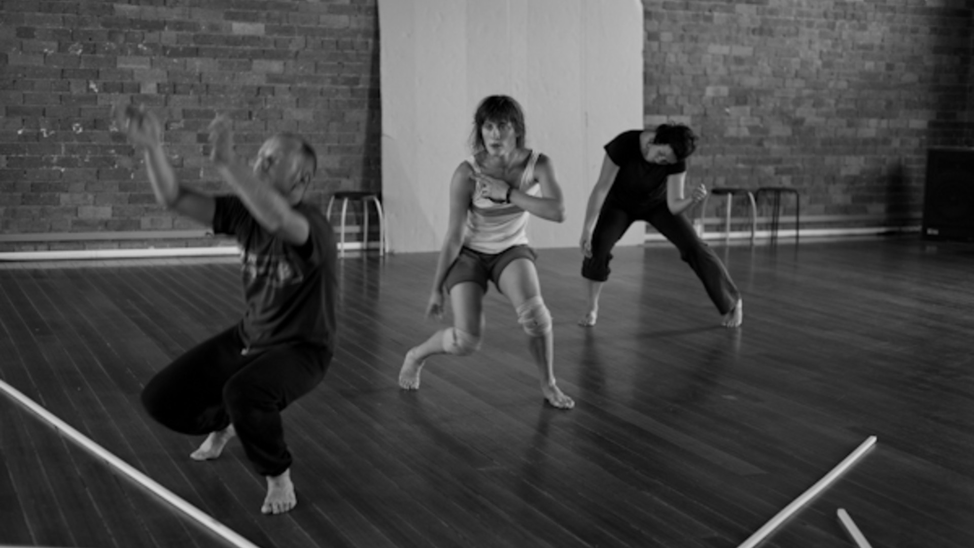 Three dancers crouch, facing different directions.